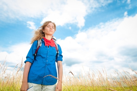 Pretty young tourist woman with closed eyes enjoying fresh air in wheat field with blue cloudy sky in background  Tourism travel and hiking outdoor in summer  photo
