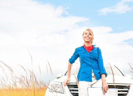 Young pretty female tourist with map in front of car  Cloudy sky and wheat field background  Happy and smiling girl looking far away  Tourism and travelling by car in summer and fall  photo