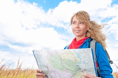 Young pretty woman tourist standing in wheat field with map  Blue cloudy sky in background behind girl  Tourism travel and hiking outdoor in summer  Healthy lifestyle  photo