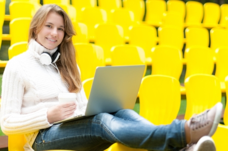 Beautiful happy student relaxing outdoor  Pretty smiling girl having break with coffee and laptop on her knees sitting in row of yellow plastic seats at school stadium  Rest from study  photo