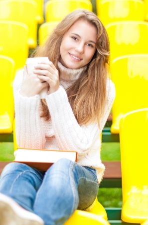 Beautiful happy student relaxing outdoor  Pretty smiling girl having break with coffee and book on her knees sitting in row of yellow plastic seats at school stadium  Rest from study