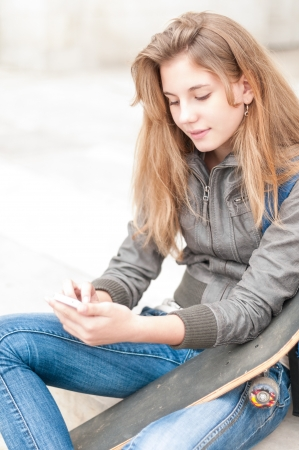 Young smiling woman sitting outdoor with skateboard and phone  Pretty female student in leather jacket and jeans having break  Free time of teenagers  Leisure and sport activity  Stock Photo - 17279126