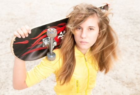 rebellious: Female teenager in gloomy mood with skateboard on her shoulder outdoor  Pretty girl with grin and bored look on her face  Free time of teenagers  Leisure and sport activity  Stock Photo