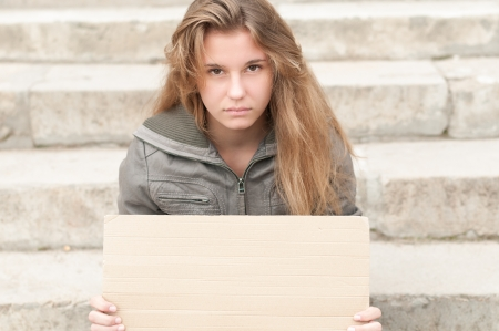 need: Abandoned teenage girl sitting outdoor on grey stone steps with blank cardboard sign in her hands  Young girl looking sad and depressed  Neglected teens  Beggar and tramp  Unemployment