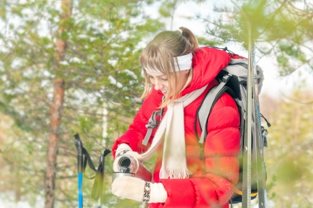Young girl in red jacket standing with backpack  Beautiful woman pouring tea from thermos and smiling  Happy blonde in sport clothes with forest as background  Outdoor skiing on winter day  Stock Photo - 17414471