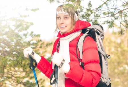 Beautiful girl in red jacket standing with backpack and ski poles  Happy smiling woman enjoys bright winter day  Winter snowy forest in background  Active sport and outdoor activity Stock Photo - 17414475
