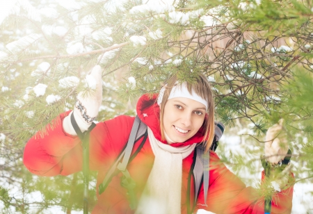 Beautiful girl in red jacket standing with backpack and ski poles  Happy smiling woman enjoys bright winter day  Winter snowy forest in background  Active sport and outdoor activity  Stock Photo - 17414470