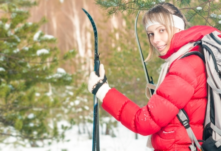 Beautiful girl in red jacket standing with backpack and ski poles  Happy smiling woman enjoys bright winter day  Winter snowy forest in background  Active sport and outdoor activity  Stock Photo - 17414469