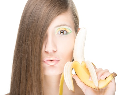 peeled banana: Beautiful young woman holding half peeled banana close to face