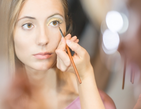 make up artist: Beautiful young woman getting make-up done  Make up artist applying eye shadow with brush  Reflection in mirror with blurs in background  Cosmetics and make-up accessories  Stock Photo