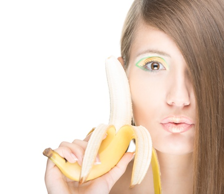peeled banana: Beautiful young woman holding half peeled banana close to face  Pretty brunette has bright make-up and half face covered with hair  Healthy food, lifestyle and diet  Summer and vitamins  Stock Photo