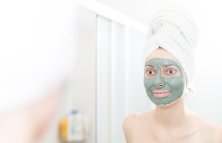 Funny woman with hair wrapped in towel  Portrait of person looking in mirror  Woman with green clay facial mask  Natural skin care therapy  Shoulders and face of female reflected in mirror of bathroom Stock Photo - 17888957