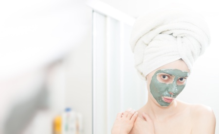 Funny woman with hair wrapped in towel  Portrait of person looking in mirror  Woman with green clay facial mask  Natural skin care therapy  Shoulders and face of female reflected in mirror of bathroom Stock Photo - 17888955