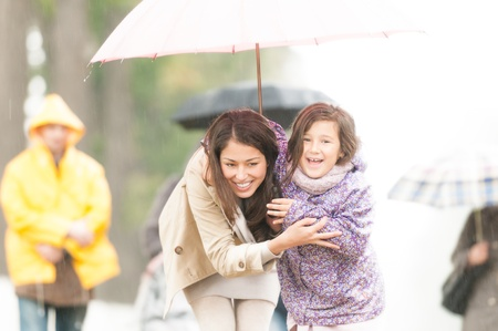 Happy mother and daughter walking in park  Smiling parent and kid hiding under umbrella  Laughing woman and child outdoors  People with umbrellas and person in yellow raincoat in background  photo