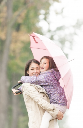 Beautiful mother embracing daughter under umbrella  Smiling woman and girl in rainy weather  Portrait of happy mom and kid  Young parent with child walking in park in autumn  Family outdoor activity