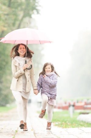 rainy day: Happy mother and daughter walking in park  Pretty woman holding umbrella  People laugh and enjoy rainy weather  Smiling parent and kid  Sky and green trees in background  Outdoor family activity