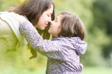 Beautiful daughter and mother looking at each other  Cute kid in jacket hugging mom, green trees in background  Happy smiling people in park  Love between child and parent  Family outdoor activity