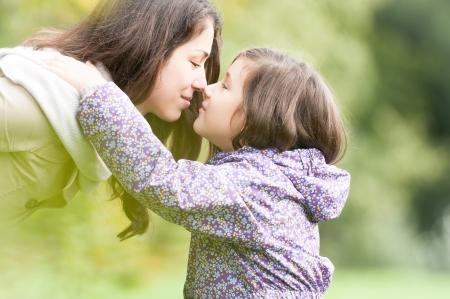 mujer hijos: Hermosa hija y madre mirando el uno al otro chico lindo en la mam� camisa abrazos, �rboles verdes en fondo feliz gente sonriente en el parque del amor entre el ni�o y la actividad principal de la familia al aire libre Foto de archivo