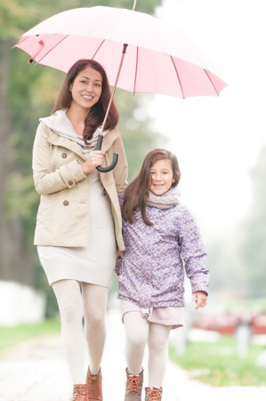 kid friendly: Young beautiful woman with pretty little daughter walking together in park under umbrella  Mother and daughter holding hands  Friendly family being happy and cheerful  Family walk outdoor in rain