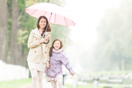 rainy: Young beautiful woman with pretty little daughter walking together in park under umbrella  Mother and daughter holding hands  Friendly family being happy and cheerful  Family walk outdoor in rain