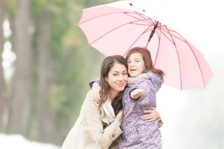rainy season: Young beautiful woman with pretty little daughter in park under umbrella  Mother and daughter together  Friendly family being happy and cheerful  Family outdoor in rain  Stock Photo