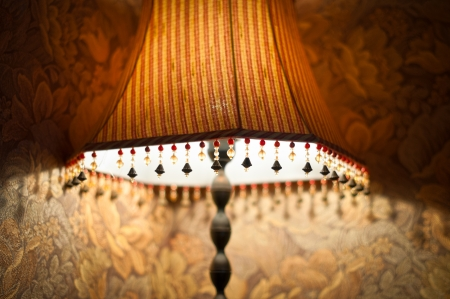 Classic vintage lamp with yellow and brown striped shade giving dim light in evening  Retro lamp decorated with beads stands near wall  Home interior and design  photo