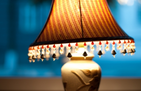 Classic vintage lamp with yellow and brown striped shade giving dim light in evening  Retro lamp decorated with beads stands near window  Home interior and design  photo