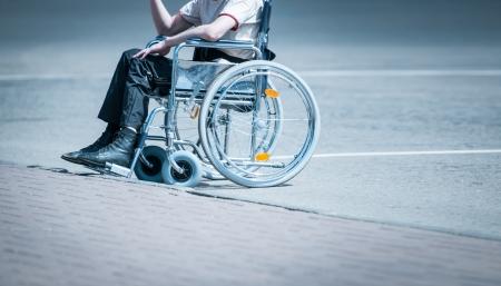 Jonge man in rolstoel op de weg in de buurt trottoir alleen zonder gezicht te zien Harde leven van mensen met een handicap Eenzaam en hulpeloos persoon Stockfoto