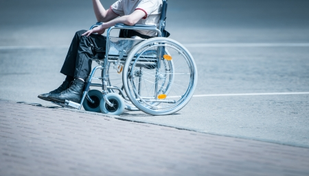 Young man in wheelchair on the road near pavement alone without face to be seen  Hard life of disabled people  Lonely and helpless person