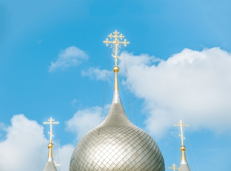 church building: Beautiful historical building  Round domes and white towers of orthodox church  Bright blue sky with white clouds at background  Sunshine reflects in domes  Main russian religious symbol