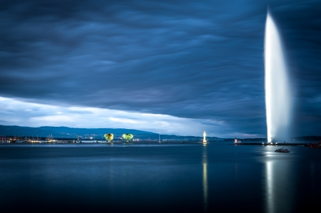 Sunset or sunrise view of the famous fountain in Geneva city in lake Geneva  Blue clouds in background  Switzerland, Europe  Stock Photo