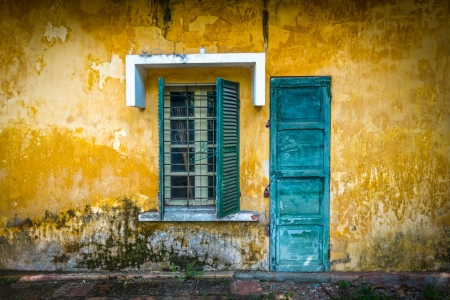stucco facade: Outside view of deserted house with details in Vietnam  Old and grungy yellow wall with window and worn blue door  Abandoned place with lock on door, half-open sun blinds and metal grating on window  Stock Photo