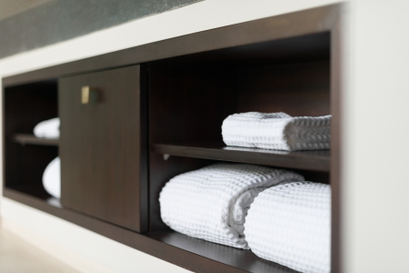 Wall with built in wooden shelf  Neat stack of white soft towels in bathroom  Closet with clean folded textile for spa and hygiene  Modern interior of hotel room  Luxury resort with classic design  photo