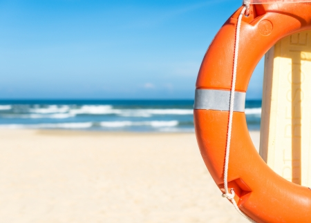 insurance services: Half of orange lifebuoy in foreground  Blue clear sky, sea and sand in background  Bright sunny day  Holidays at beach  Beautiful seascape  Equipment for rescue of people  Service for lifesaving