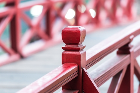 Close-up view of wooden bridge in Vietnam with blurry background and rails in foreground  Rich cherry color of handrails with geometric pattern  Architecture of East