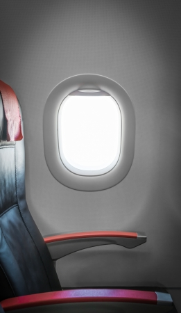 armrest: Side view of single empty seat in passenger airplane  Comfortable leather black seat with red armrests  Window with sunlight aside  Interior of plane  Travelling with comfort by air  Economy class