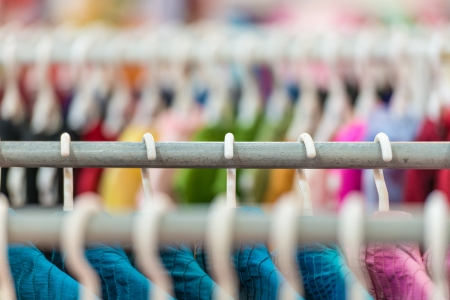 Rows of new colorful clothing on hangers at shop in foreground and background  版權商用圖片
