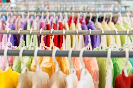 Rows of new colorful clothing on hangers at shop in foreground and background   photo