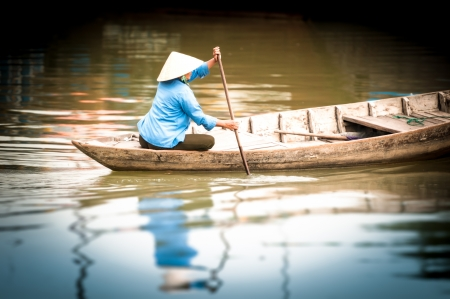 rowing: Woman in conical hat sitting on canoe and rowing   Stock Photo