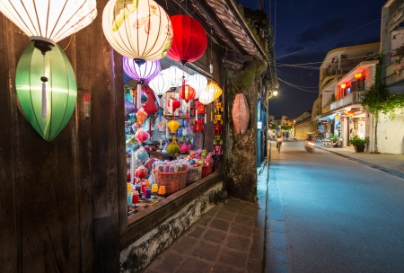 Wide view on narrow street in Hoi An town in Vietnam and shop on left with big bright window and multicolored lanterns over it  Houses going into distance on right  Travelling and tourism