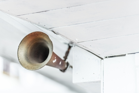 informing: Close up view of old grungy metal horn on ship under old white wooden ceiling  Sound signal during sea travelling  Way of warning or informing passengers about danger  Safety on board