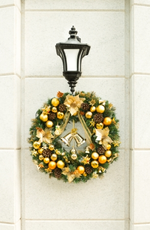 Beautiful Christmas wreath with golden balls, bells and pine cones hanging on lantern on white stone wall in street  Traditional festive decorations and design  Christmas and New Year holidays  photo