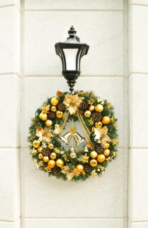 festal: Bella corona di Natale con le palle d'oro, campane e pigne appese lanterna su bianco muro di pietra in strada decorazioni festive tradizionali e di design di Natale e Capodanno