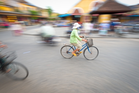 Asian woman riding blue bike  Person on bicycle  Crossroad of Hoi An in Vietnam, Asia  Blur motion of busy street with houses and transport  Famous destination for tourists  Eastern city life  photo