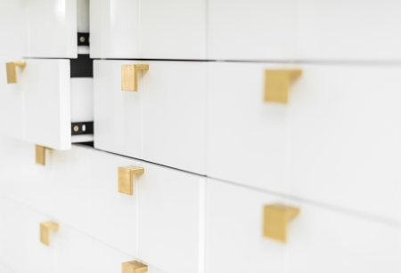 sleek: Rows of white sleek drawers with golden handles in strict geometric style  Two half-opened drawers in background  House or office interior  Furniture and keeping things