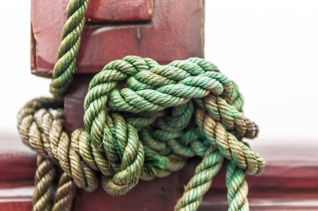 mooring: Marine rope tied into knot in foreground, white background  Close-up of nautical equipment for mooring  Focus on detail of ship  Green twisted rope wrapped around red wooden deck  Sea travel
