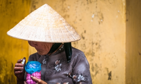 adult vietnam: Old poor woman wearing conical hat and traditional asian dress  Vietnamese lady holding pink and blue jar  Wrinkled face under headwear  Elderly person standing near yellow wall in Vietnam, Asia  Stock Photo