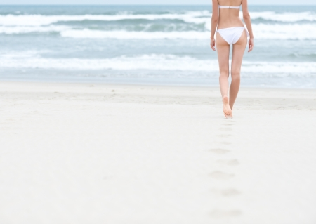 gentle dream vacation: Young slim woman in white swimsuit walking to sea or ocean leaving footprints on soft sand  Blue ocean waves with foam in background  Bathing or sunbathing on beach  Holidays and vacations in summer