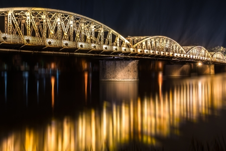 Panoramic view of Truong Tien Bridge in Hue City at night  Bridge illuminated all over with blurry reflection on water  Columns of light rise skyward  Famous sights of Vietnam  Travelling and tourism  Stock Photo