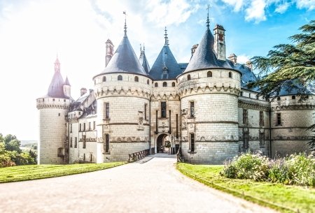 Grand castle in France, Europe. Chateau of white stone with towers surrounded with green lawns and trees. Road leading to entrance in foreground, blue cloudy sky in background. Architecture of Europe. Editorial